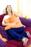 Mujer hermosa feliz que habla en el teléfono en casa que sonríe Fotografía de archivo libre de regalías