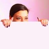 Mujer hermosa feliz que mira a escondidas detrás de un whiteboard Foto de archivo