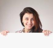 Mujer hermosa feliz que mira a escondidas detrás de un whiteboard Fotos de archivo libres de regalías