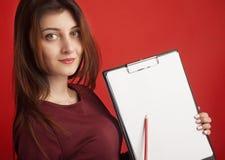 Mujer hermosa feliz que mira a escondidas en el tablero blanco Imagenes de archivo