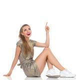 Mujer hermosa feliz que se incorpora y que señala Imagenes de archivo