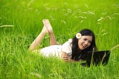 Mujer hermosa feliz que usa la computadora portátil al aire libre Imagen de archivo libre de regalías