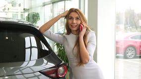 Mujer hermosa feliz que usa su teléfono elegante en el salón de la concesión de coche metrajes