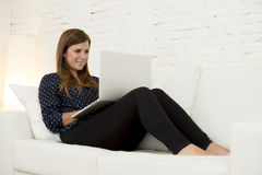 Mujer hermosa feliz 30s que usa la sala de estar moderna sonriente del establecimiento de una red del ordenador portátil en casa  Imagenes de archivo