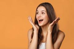 Mujer hermosa feliz sorprendida que mira de lado en el entusiasmo Aislado en fondo anaranjado foto de archivo