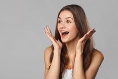 Mujer hermosa feliz sorprendida que mira de lado en el entusiasmo Aislado en fondo gris foto de archivo libre de regalías