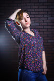 Mujer hermosa informal que presenta contra una pared de ladrillo Fotos de archivo