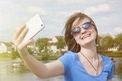 Mujer hermosa, instagram mujer que toma un selfie con el teléfono elegante al aire libre en la ciudad en día de verano soleado Ti Fotografía de archivo