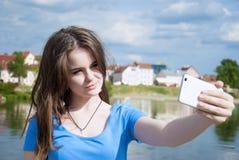 Mujer hermosa, instagram mujer que toma un selfie con el teléfono elegante al aire libre en la ciudad en día de verano soleado Ti Foto de archivo