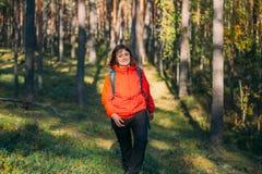 Mujer hermosa joven activa de CaucasianLady vestida en la chaqueta roja que camina en la edad de Autumn Forest Active Lifestyle I imágenes de archivo libres de regalías