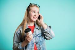 Mujer hermosa joven alegre en vidrios que habla en el teléfono y que mira a un lado con sonrisa y que sostiene el café foto de archivo