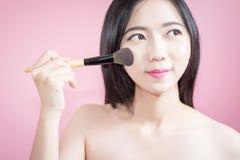 Mujer hermosa joven asiática del pelo largo que aplica el cepillo cosmético del polvo en la cara lisa aislada sobre fondo rosado  Fotografía de archivo