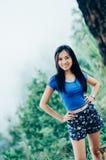 Mujer hermosa joven asiática en una camiseta azul en un acantilado de un MES Fotos de archivo