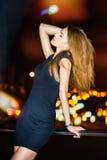 Mujer hermosa joven atractiva que presenta sobre fondo de la ciudad de la noche Foto de archivo