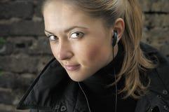 Mujer hermosa joven con el earbud. Imágenes de archivo libres de regalías