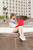 Mujer hermosa joven con el ordenador portátil que se sienta en las escaleras cerca de la universidad Imagen de archivo libre de regalías