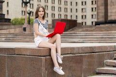Mujer hermosa joven con el ordenador portátil que se sienta en las escaleras cerca de la universidad Imagenes de archivo