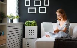 Mujer hermosa joven con el ordenador portátil y la taza de café en morni Fotografía de archivo