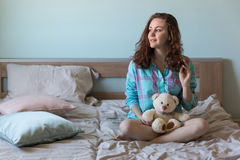 Mujer hermosa joven con el oso de peluche en cama Fotografía de archivo