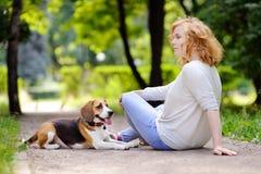 Mujer hermosa joven con el perro del beagle fotografía de archivo