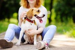 Mujer hermosa joven con el perro del beagle en el parque Foto de archivo