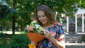 Mujer hermosa joven con el ramo de flores almacen de metraje de vídeo