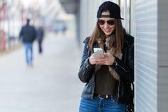 Mujer hermosa joven con el teléfono móvil en la calle Fotos de archivo libres de regalías