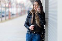 Mujer hermosa joven con el teléfono móvil y el café Imagenes de archivo