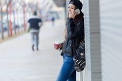 Mujer hermosa joven con el teléfono móvil y el café Imágenes de archivo libres de regalías