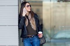 Mujer hermosa joven con el teléfono móvil y el café Foto de archivo libre de regalías