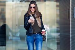 Mujer hermosa joven con el teléfono móvil y el café Fotografía de archivo libre de regalías