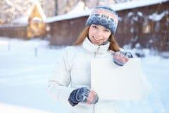 Mujer hermosa joven con la bandera en blanco. Invierno. Imagen de archivo libre de regalías