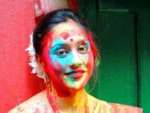 Mujer hermosa joven con la cara pintada que celebra Holi Fotos de archivo