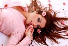 Mujer hermosa joven con la flor rosada fotografía de archivo libre de regalías