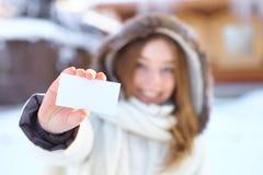 Mujer hermosa joven con la tarjeta de visita en blanco. Invierno. Fotos de archivo