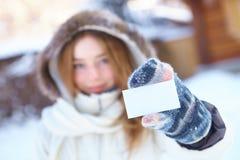 Mujer hermosa joven con la tarjeta de visita en blanco. Invierno. Imágenes de archivo libres de regalías