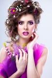 Mujer hermosa joven con las flores en su pelo y maquillaje brillante Imágenes de archivo libres de regalías