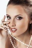 Mujer hermosa joven con las perlas de la joyería Fotografía de archivo