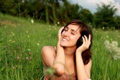 Mujer hermosa joven con los auriculares Fotos de archivo libres de regalías
