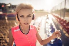 Mujer hermosa joven con los auriculares que presentan sobre asientos del voleo de la playa Imagen de archivo