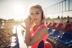 Mujer hermosa joven con los auriculares que presentan sobre asientos del voleo de la playa Fotografía de archivo