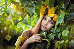 Mujer hermosa joven con los ojos verdes en una guirnalda amarilla en hojas verdes Imágenes de archivo libres de regalías