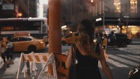 Mujer hermosa joven con los panieres que camina adentro centro de la ciudad de Nueva York, América, cruzando el camino del tráfic almacen de metraje de vídeo