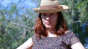 Mujer hermosa joven con los pelos rojos que sientan el exterior que mira la cámara y después que mira para arriba seriamente almacen de video