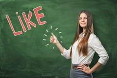 Mujer hermosa joven con los pulgares encima del gesto que se coloca cerca de palabra roja grande 'como' escrito en la pizarra ver imagen de archivo libre de regalías