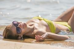 Mujer hermosa joven con los vidrios que mienten sobre el suyo detrás en el agua en la playa arenosa Foto de archivo