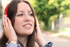 Mujer hermosa joven con música que escucha de los auriculares Fotografía de archivo libre de regalías