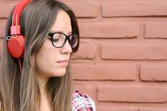 Mujer hermosa joven con música que escucha de los auriculares Foto de archivo libre de regalías