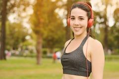 Mujer hermosa joven con música que escucha de los auriculares rojos Imagen de archivo
