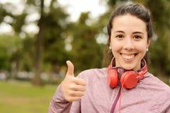 Mujer hermosa joven con música que escucha de los auriculares rojos Foto de archivo